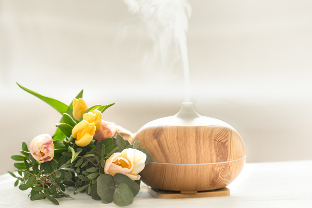 aroma-oil-diffuser-lamp-table-blurred-with-beautiful-spring-bouquet-tulips_169016-4239